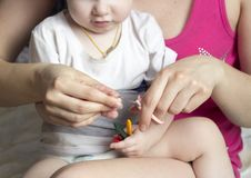 Girl mother cuts her nails in the hands of a little girl scissor royalty free stock image