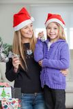 Girl With Mother Decorating Christmas Tree Stock Photo