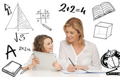 Girl and mother doing homework with tablet pc Stock Photos