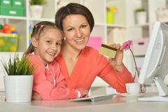 Girl  with mother doing shopping online Royalty Free Stock Photos