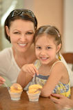 Girl and mother eating ice creams Stock Photos