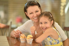 Girl and mother eating ice creams. Little cute girl eating ice creams with her mother Royalty Free Stock Photos