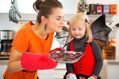 Girl with mother enjoying the aroma of Halloween biscuits Stock Photo