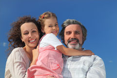 Girl, mother and grandfather smiling and embracing Stock Images