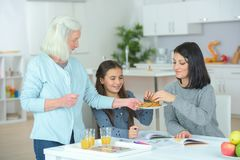 Girl with mother and grandmother eating creps at home stock images
