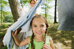 Girl and mother hanging clothes in forest Royalty Free Stock Photography