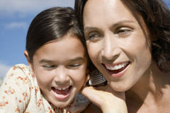Girl And Mother Listening To Cell Phone Stock Image