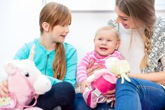 Girl and mother looking at happy baby stock photography