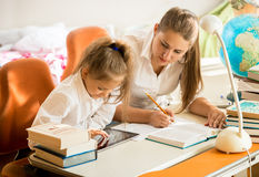 Girl with mother looking on tablet how to do homework Stock Photo