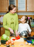 Girl and mother making soup Stock Photography