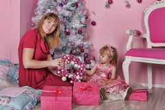 Girl and mother near Christmas fir-tree Stock Images