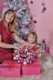 Girl and mother near Christmas fir-tree Stock Photos