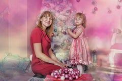 Girl and mother near Christmas fir-tree Royalty Free Stock Photos