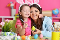 Girl with mother painting eggs. Little girl with mother painting eggs for Easter holiday Stock Images