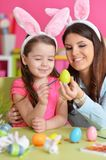 Girl with mother painting eggs. Little girl with mother painting eggs for Easter holiday Royalty Free Stock Images