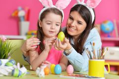 Girl with mother painting eggs. Little girl with mother painting eggs for Easter holiday Royalty Free Stock Photography
