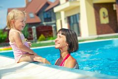 Girl with mother in the pool Stock Image