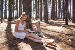 Girl and mother reading the book. In the woods Stock Images