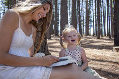 Girl and mother reading the book. In the woods Royalty Free Stock Images