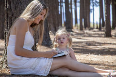 Girl and mother reading the book. In the woods Royalty Free Stock Photos