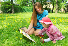 Girl and mother reading the book in spring park Stock Photo
