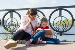 Girl and mother reading the book. Urban background, river, sky stock photography