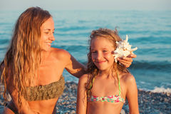 Girl with mother on sea background Stock Images