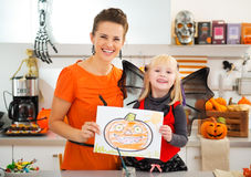Girl with mother showing halloween Jack-O-Lantern drawing Stock Photos