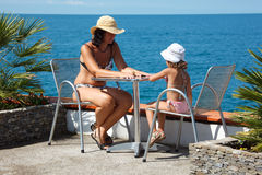 Girl with mother sitting at table under open sky Stock Images