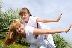 Girl with mother in spring park. Happy girl and her mother in the spring park among flowers Stock Photography