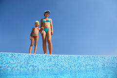 Girl with mother stand on skirting of pool Royalty Free Stock Image