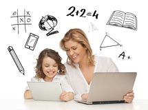 Girl and mother with tablet and laptop. Education, technology, internet and parenting concept - girl and mother with tablet and laptop stock images