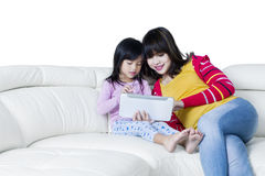 Girl and mother with tablet relaxing on sofa Royalty Free Stock Photos