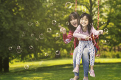 Girl and mother touching bubbles Stock Photo