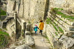 Girl with mother walking along medieval wall Stock Photo