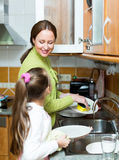 Girl  with mother washing dishes Royalty Free Stock Photos