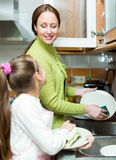 Girl  with mother washing dishes Stock Photo