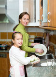 Girl  with mother washing dishes Stock Photos