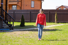 Girl in motion. Goes on lawn Stock Photo