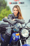 Girl in moto equipment with a motorcycle Royalty Free Stock Photography