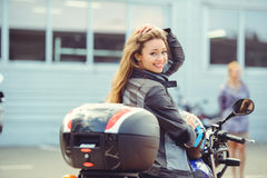 Girl in moto equipment with a motorcycle. Girl in moto gear sits on a motorcycle posing, looking back beautiful smiling with well-groomed hair Royalty Free Stock Photos