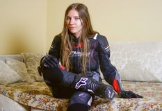 Girl in Moto gear. Leather pants and leather jacket, gloves and. Boots royalty free stock image