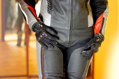 Girl in Moto gear. Leather pants and leather jacket and gloves. Hands on his belt Stock Photography