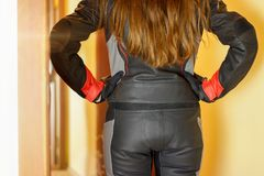 Girl in Moto gear. Rear view. Leather pants and leather jacket a royalty free stock images