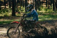 Girl motocross racer rides through a puddle Royalty Free Stock Photos