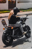 Girl & motorbike. Gilr riding motorbike with a black leather jacket. Biker style with a british bobber style bike Stock Photo