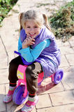 Girl on the motorbike. Happy child sitting on the pink motorbike Stock Photos