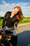 Girl on a motorbike on a road Stock Photography