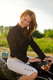 Girl on a motorbike on a road Stock Images