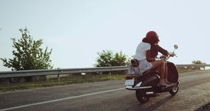 The girl on the motorbike is waving her hands into the air being all excited going on a long distance journey with her. Lover stock video footage